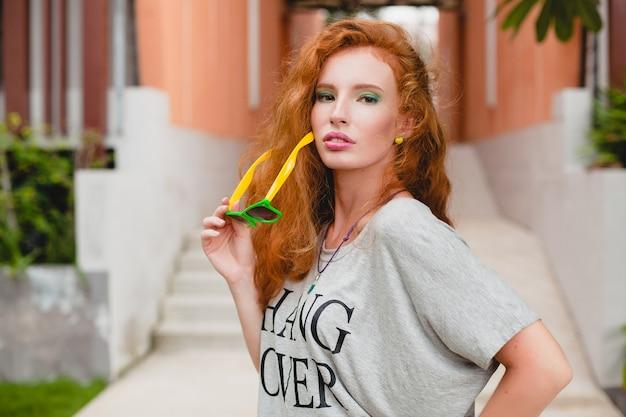 フィットネスアパレル、生姜髪、緑のショートパンツ、サングラス、特大のtシャツ、ハングオーバー、パーティー気分の若いスタイリッシュな女性。楽しんで、セクシーで、熱く、軽薄で、スリムな体で、運動して、