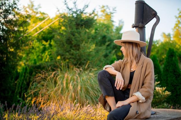 Молодая стильная женщина в шляпе, сидя возле цветов лаванды в саду