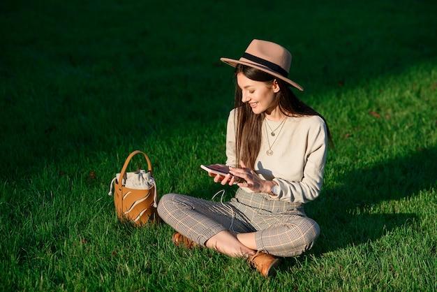 帽子をかぶった若いスタイリッシュな女性は、夏の朝に緑の芝生に座って携帯電話を使用しています。