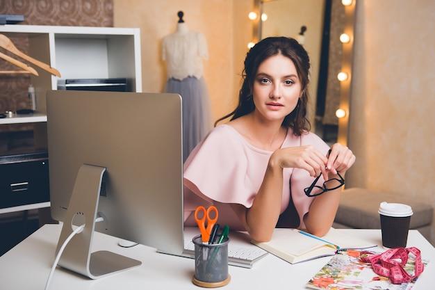 Молодая стильная женщина в розовом роскошном платье, работающая в офисе на компьютере