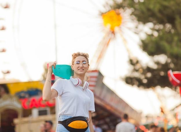 Молодая стильная женщина в стильной молодежной одежде со скейтбордом на плечах веселится в парке развлечений