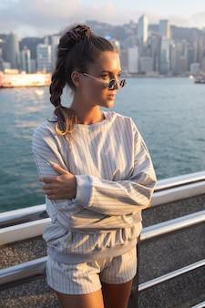 세련된 젊은 여성이 홍콩 빅토리아 항구에서 포즈를 취하고 있습니다.