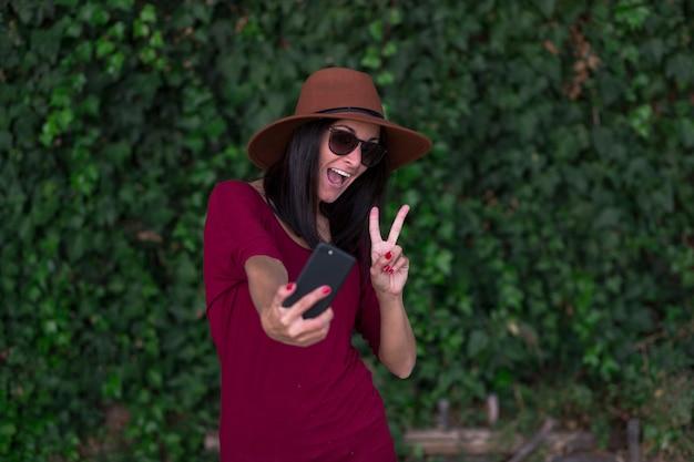 Молодая стильная женщина, делающая селфи по зеленому плющу, оставляет фон, нося стильную коричневую шляпу, красную футболку и солнцезащитные очки, делая селфи и весело проводя время.
