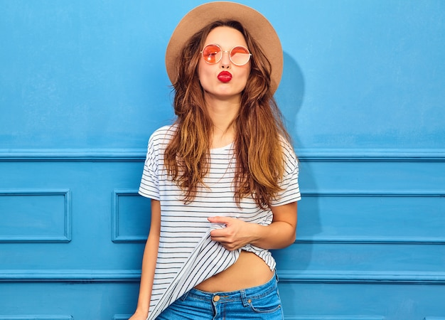 Young stylish woman model in casual summer clothes and brown hat with red lips, posing near blue wall. giving air kiss