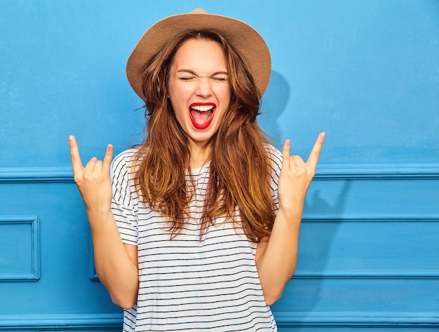 Young stylish woman model in casual summer clothes and brown hat with red lips, posing near blue wall. showing rock and roll sign
