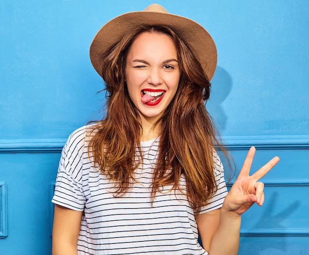 Young stylish woman model in casual summer clothes  and brown hat with red lips, posing near blue wall. winking and showing peace sign