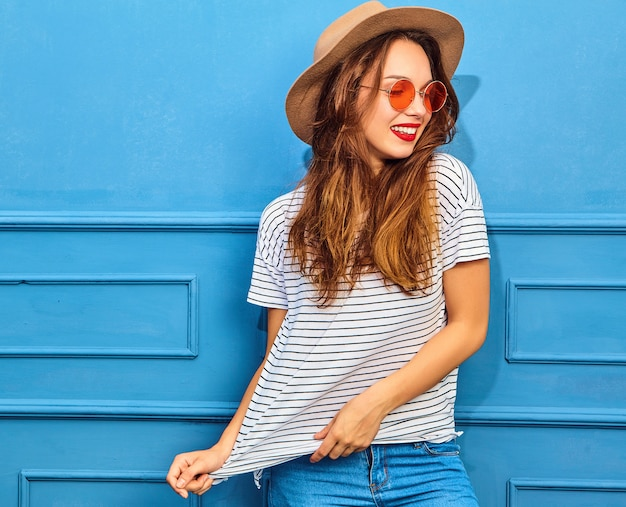 Young stylish woman model in casual summer clothes and brown hat with red lips, posing near blue wall