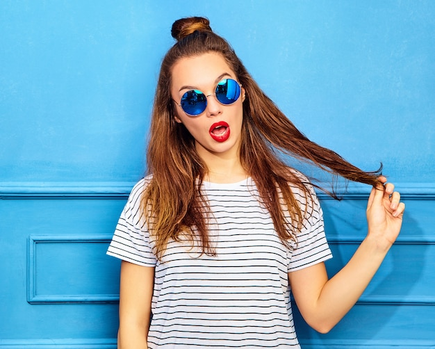 Young stylish woman model in casual summer clothes with red lips, posing near blue wall. playing with her hair