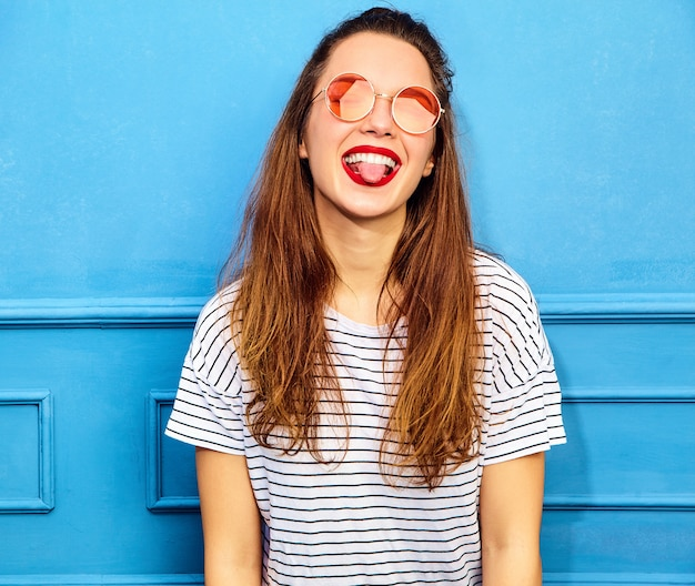 Young stylish woman model in casual summer clothes with red lips, posing near blue wall. showing her tongue