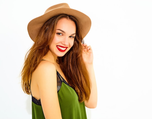 Young stylish woman model in casual summer green clothes and brown hat with red lips, posing near white wall