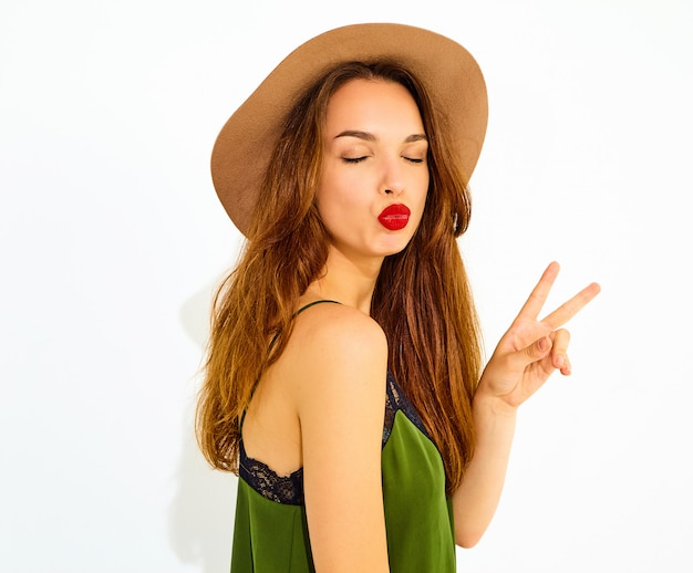 Young stylish woman model in casual summer green clothes and brown hat with red lips. showing peace sign and giving kiss