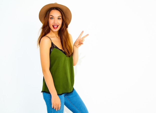 Young stylish woman model in casual summer green clothes and brown hat with red lips, showing peace sign and her tongue