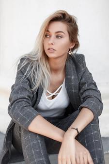 재킷과 바지와 세련된 회색 봄 정장에 세련된 젊은 여성 모델은 거리에 흰 벽 근처에 앉아