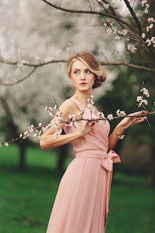 Young stylish woman near blossoming flowering tree in the park. spring wall. blonde girl with hairstyle in pink dress. copy space.
