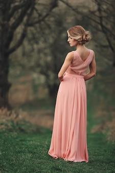 Молодая стильная женщина на открытом воздухе в парке весны. блондинка с прической в длинном розовом платье possing. выборочный фокус. вид сзади