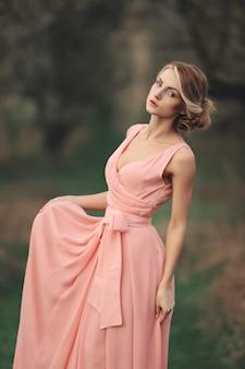 春の公園で屋外のスタイリッシュな若い女性。ピンクのドレスpossingの髪型とブロンドの女の子。セレクティブフォーカス