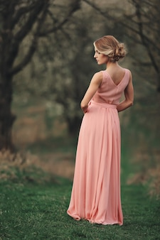 Young stylish woman outdoors in the spring park. blonde girl with hairstyle in long pink dress possing. selective focus. back side view