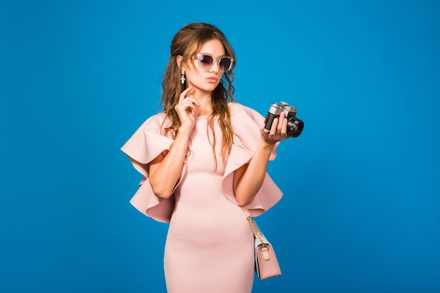 Young stylish woman in pink luxury dress with retro camera
