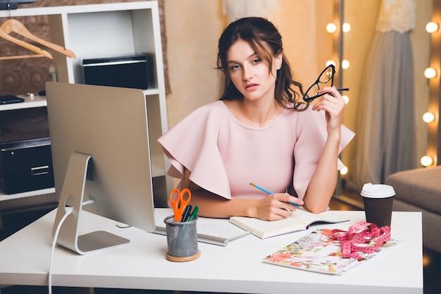 Giovane donna alla moda in vestito di lusso rosa che lavora all'ufficio sul computer