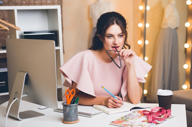 Young stylish woman in pink luxury dress working at office on computer