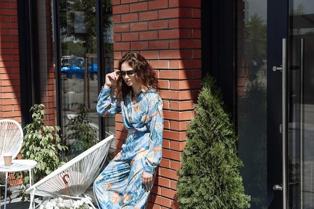 새로운 여름 옷 광고 컬렉션에서 벽 배경에 포즈를 취한 세련된 젊은 여성