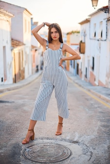 Young stylish woman posing against the old narrow street and buildings.
