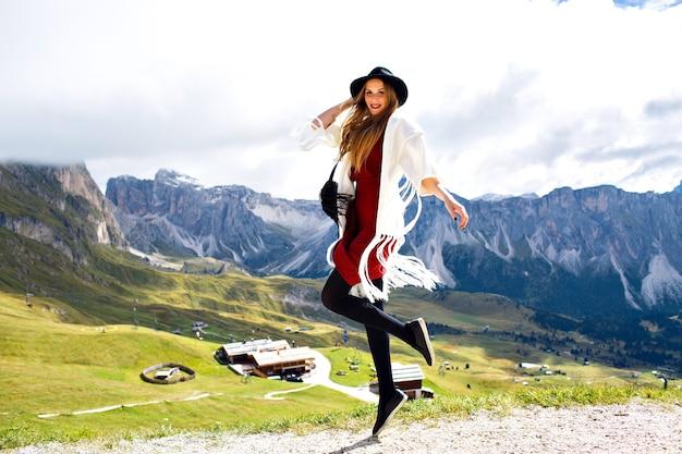 Молодая стильная женщина позирует в альпах в модном наряде бохо
