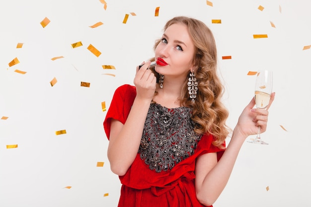 Young stylish woman in red evening dress celebrating new year using red lipstick and holding glass of champagne