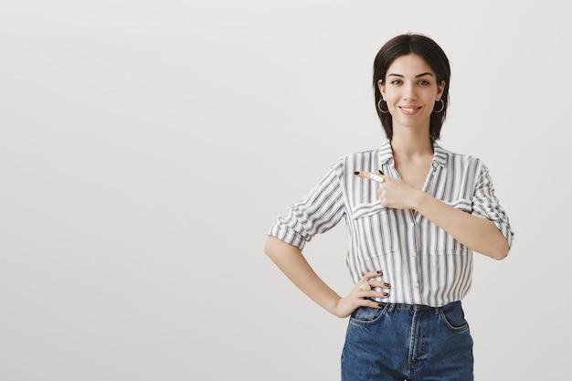 Молодая стильная женщина показывает объявление, указывая пальцем влево и улыбается