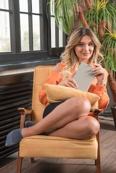 Giovane donna alla moda che si siede in poltrona che tiene il libro mentre sorride.