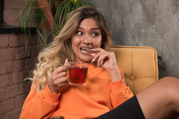 Young stylish woman sitting in armchair holding cup of tea and eating cookie.