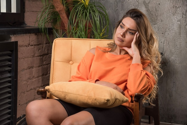Giovane donna alla moda seduto in poltrona mentre pensa a qualcosa.