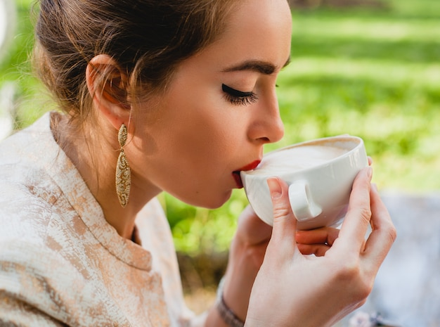 Young stylish woman, sitting in cafe, holding cup of cappuccino