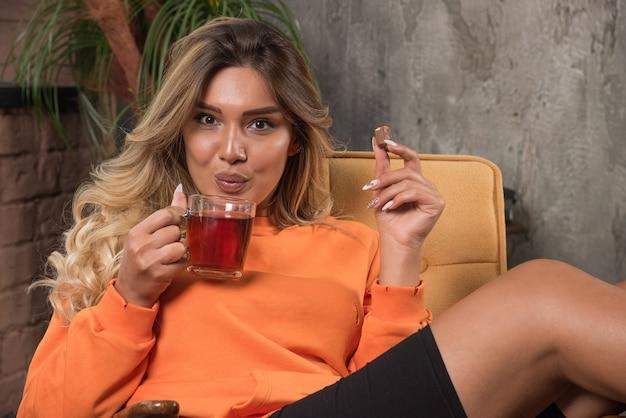 차 한잔 불고 안락의 자에 앉아 젊은 세련 된 여자.