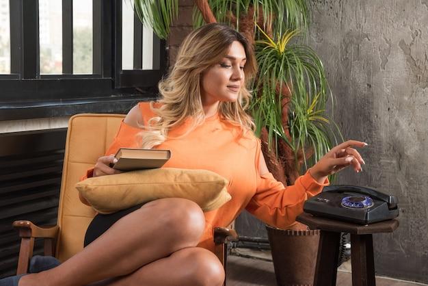 안락의 자 전화 걸기에 앉아 젊은 세련 된 여자.