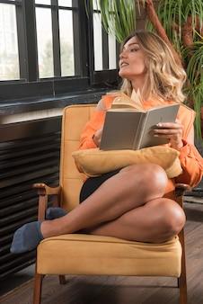 측면을보고 책을 들고 안락의 자에 앉아 젊은 세련 된 여자.