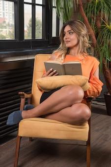 창에서 보는 동안 책을 들고 안락의 자에 앉아 젊은 세련 된 여자.