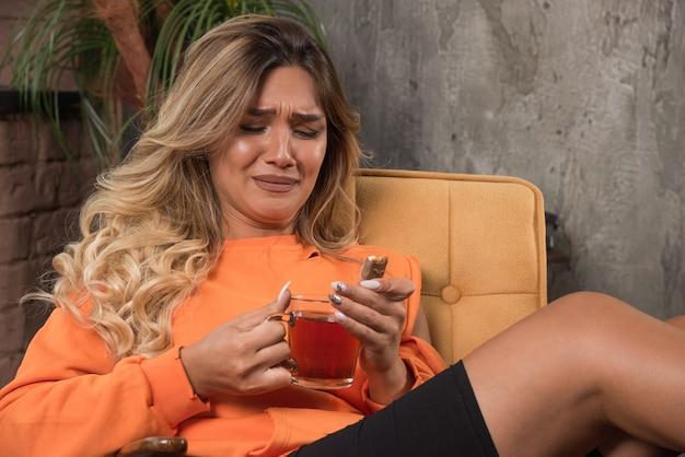 차 한잔 들고 먹고하려고 안락의 자에 앉아 젊은 세련 된 여자.