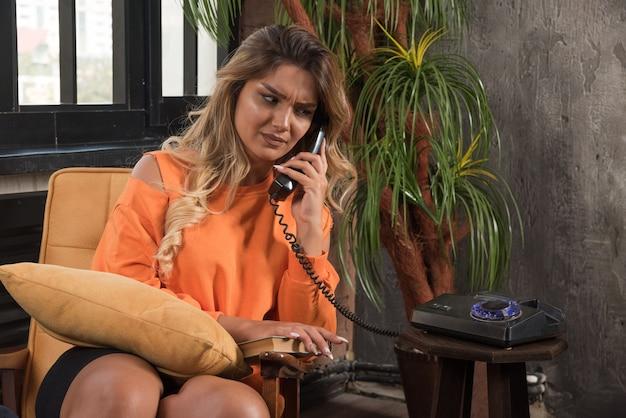화가 나 전화로 얘기 안락의 자에 앉아 젊은 세련 된 여자.
