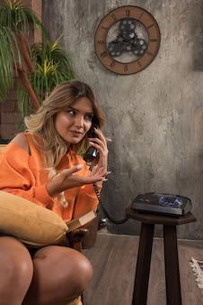 심각한 비즈니스에 대 한 전화로 얘기 안락의 자에 앉아 젊은 세련 된 여자.