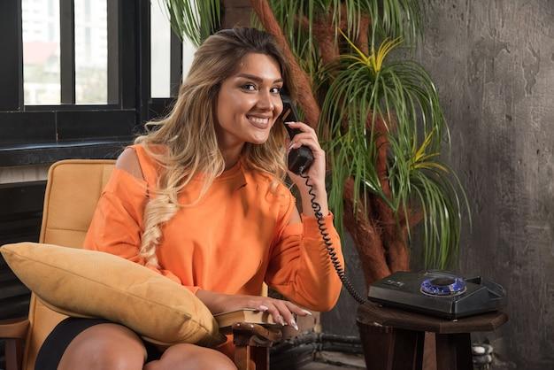 전화로 행복 하 게 얘기하는 안락의 자에 앉아 젊은 세련 된 여자.