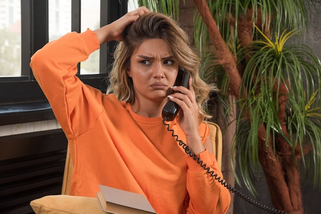 그녀의 머리를 들고 전화로 얘기하는 안락의 자에 앉아 젊은 세련 된 여자.