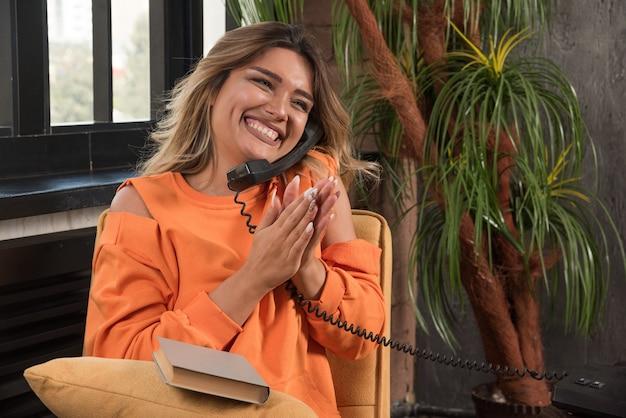 전화로 얘기하는 안락의 자에 앉아 젊은 세련 된 여자.