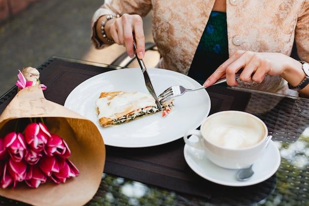 Молодая стильная женщина сидит в кафе, ест вкусный пирог
