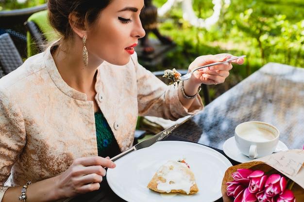 カフェに座って、おいしいパイを食べる若いスタイリッシュな女性