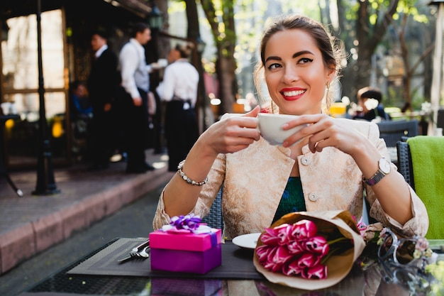 カプチーノのカップを保持しているカフェに座っている若いスタイリッシュな女性