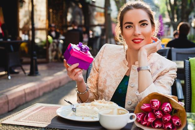 Молодая стильная женщина сидит в кафе, держа подарочную коробку, улыбаясь