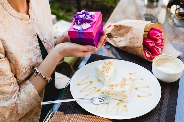 プレゼントボックスを保持しているカフェに座っている若いスタイリッシュな女性