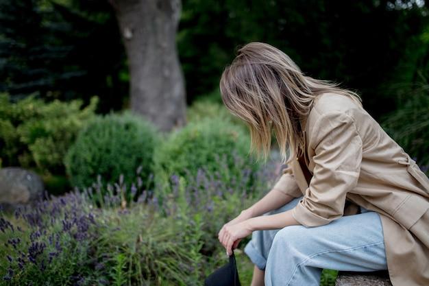 Молодая стильная женщина, сидящая возле цветов лаванды в саду