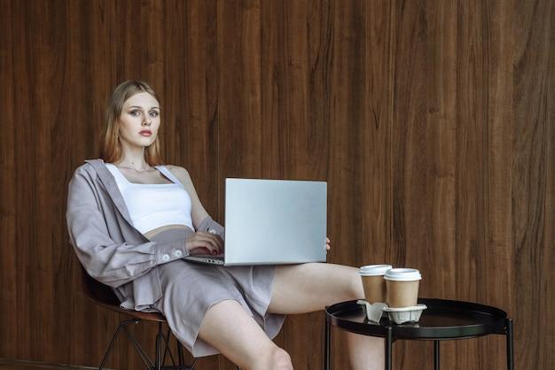노트북과 함께 앉아서 카메라를 보고 있는 젊은 세련된 여성